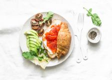 Morning breakfast table - croissant with cream cheese and smoked salmon, avocado and cherry tomatoes. Delicious balanced breakfast royalty free stock photography