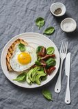 Morning breakfast table. Fried egg grilled sandwich and spinach, tomato, avocado salad on a gray background stock images
