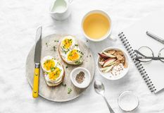 Morning breakfast table inspiration - sandwiches with cream cheese and boiled egg, yogurt with apple and flax seeds, herbal detox royalty free stock photo