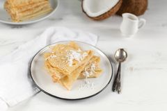 Morning, breakfast - traditional russian blini pancakes, french crepes, fresh coconut, milk bottle, white ceramic pitcher royalty free stock photography