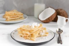 Morning, breakfast - traditional russian blini pancakes, french crepes, fresh coconut, milk bottle, white ceramic pitcher royalty free stock photo