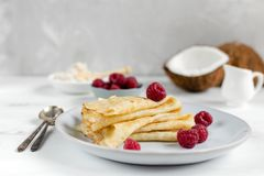 Morning, breakfast - traditional russian blini pancakes, french crepes served with fresh raspberries, coconut. White wooden table stock photography
