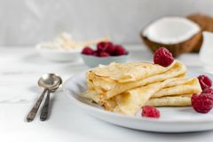 Morning, breakfast - traditional russian blini pancakes, french crepes served with fresh raspberries, coconut. White wooden table royalty free stock images
