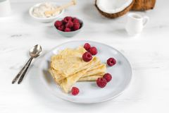 Morning, breakfast - traditional russian blini pancakes, french crepes served with fresh raspberries, coconut. White wooden table royalty free stock photos