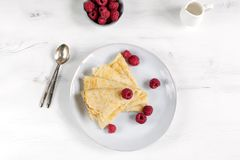 Morning, breakfast - traditional russian blini pancakes, french crepes served with fresh raspberries, coconut. White wooden table, top view royalty free stock photo