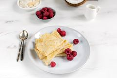 Morning, breakfast - traditional russian blini pancakes, french crepes served with fresh raspberries, coconut. White wooden table, top view royalty free stock photography