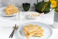 Morning, breakfast - traditional russian blini pancakes, french crepes whipped cream, cast iron green teapot, mimosa flower. White wooden table royalty free stock photography
