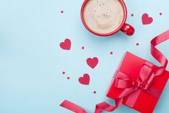 Morning breakfast for Valentines day. Coffee, gift box, paper heart and confetti on blue background top view. Flat lay. stock images