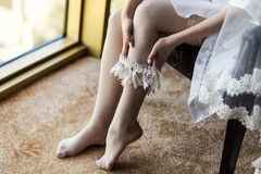 Morning of the bride, the bride wears a wedding garter on leg, a. Wedding, a beautiful dress Royalty Free Stock Photo