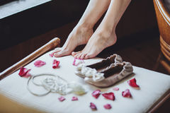 Morning bride. Brides feet close up, wedding shoes, rose petals Stock Photos