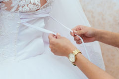 Morning bride. Bridesmaid helping the  lacing up her dress Royalty Free Stock Image