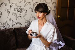Morning of the bride. Girl drinks coffee from a white cup. Wedding ceremony Royalty Free Stock Photo