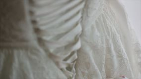 Morning bride. maid of honor helping the bride with her dress. the bride`s lace up dress. Bridesmaid tying bow on. Wedding dress. Woman`s hands lace up silk stock video footage