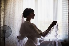 Morning of the bride. Wedding ceremony. The girl in a white dress and veil. Put on clothes. Female portrait Stock Photo