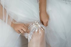 In the morning, the bride in stockings and a white wedding dress wears a garter on her leg, the bride is holding her hands for the stock photos