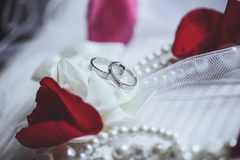 Morning bride. Wedding rings, rose petals and pearl necklace. We Royalty Free Stock Photography