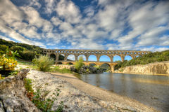 Morning at the bridge aqueduct Pont du Gard. This is a wide shot of part of the ancient Roman aqueduct, the bridge Pont du Gard, whose archways span the Gardon Stock Photo