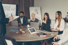 Morning briefing. Business team on a morning briefing; business meeting and presentation in a modern office. Focus on the people on the left Royalty Free Stock Image