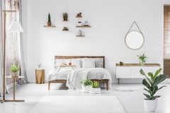 Morning in a bright and sunny modern white bedroom interior with. Wooden furniture. Cushions, blanket and food tray on the bed, nightstand beside and hanging Royalty Free Stock Images