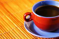 Morning caffeine. Vivid colored cup on an orange natural background Stock Images