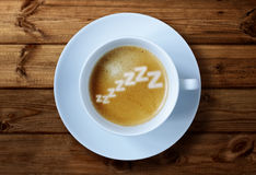 Morning caffeine. Coffee cup with zzzzzzz in the froth concept for exhaustion, overworked and feeling tired Stock Photography