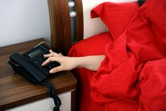 Morning call. A girl offers her hand from quilt to answer a call Stock Photos