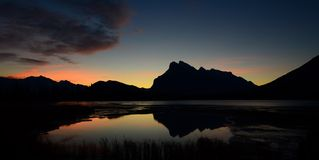 Morning Calm. Mount Rundle in silhouette from the morning sun, reflected in the calm waters of Vermillion Lakes, Alberta royalty free stock photos