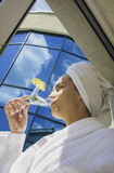Morning Cap. Young woman wearing bath robe and drinking a Martini Stock Photo