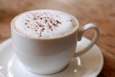 Morning Cappuccino. A frothy Italian cappuccino on a wooden table Stock Image