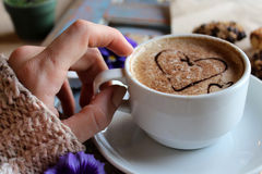 Morning cappuccino with hearts, with cookies and flowers. Morning cappuccino in women hands with hearts, with cookies and flowers stock photo