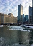 Morning in Chicago with interesting cloudscape over icy Chicago River in winter. Royalty Free Stock Photo