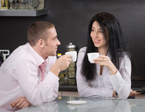 Morning coffee. Happy young couple having their morning coffee in the kitchen royalty free stock photos