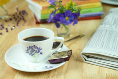 Morning coffee. A cup of morning coffee surrounded with newspaper, colorful flowers and books. Optimistic day Royalty Free Stock Photography
