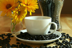 Morning coffee. Cup of black coffee and beans. Composition with flowers Royalty Free Stock Image
