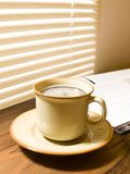 Morning coffee. A cup of hot coffee, and newspaper. Wood table royalty free stock photos