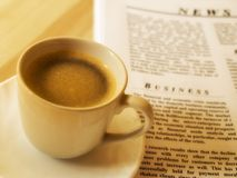 Morning coffee. A cup of hot coffee, and newspaper. Wood table stock images