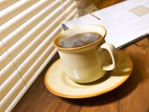 Morning coffee. A cup of hot coffee, and newspaper. Wood table stock photography