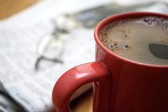 Morning coffee. A cup of coffee, a newspaper and a pair of glasses, on a wooden table Royalty Free Stock Photos