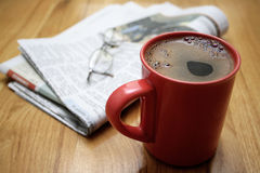 Morning coffee. A cup of coffee, a newspaper and a pair of glasses, on a wooden table Royalty Free Stock Photo
