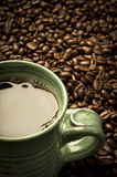 Morning Coffee. Green coffee cup resting in a pile of coffee beans Stock Photo