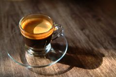 Morning Coffee. A glass cup of crema black coffee on a wooden table in the morning sunlight Stock Photos