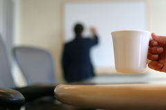 Morning coffee. Businessman writing on white board, hand visible in foreground holding a cup of coffee Stock Image