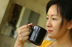 Morning Coffee. An asian lady having her morning coffee Stock Photo
