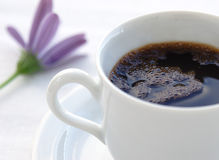 Morning coffee. Fresh black coffee, puple flower in the background royalty free stock image