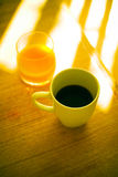 Morning coffee. Cup of coffee and glass of orange juice on wooden table, in the morning Stock Image