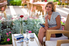 Morning coffee. Young woman thinking at coffee table at terrace Royalty Free Stock Images