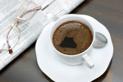 Morning Coffee. Cup of coffee, news and glasses on the table royalty free stock image