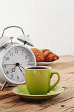 Morning coffee with alarm clock on a rustic wooden table Royalty Free Stock Images