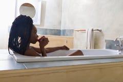 Morning coffee in bath tub. Beautiful woman with afro hair dreaming in bath tub stock photo