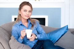 Morning coffee for a beautiful girl. A beautiful girl sits on a soft sofa, holds a mug of hot coffee in her hands and looks at you with a smile Stock Images